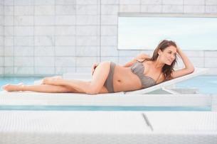 Mid adult woman in bikini lying on pool sunbedの写真素材 [FYI03506320]