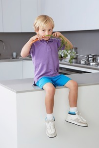 Boy sitting on side in kitchen with carrot moustacheの写真素材 [FYI03506364]