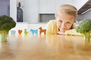 Girl playing with toy animals around broccoliの写真素材 [FYI03506377]