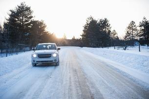 Car driving along road in snowの写真素材 [FYI03507071]