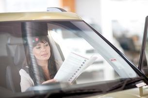 Mid adult woman reading car brochure in showroomの写真素材 [FYI03507370]