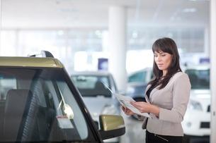 Mid adult woman checking car brochure in showroomの写真素材 [FYI03507378]
