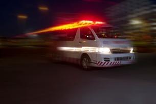 Emergency ambulance speeding through city at nightの写真素材 [FYI03507431]