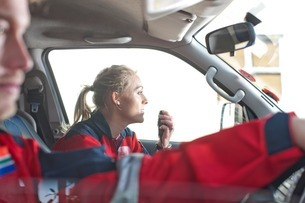 Paramedics driving to emergency in ambulanceの写真素材 [FYI03507449]