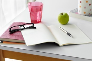Kitchen table still life with notebooks, spectacles and applの写真素材 [FYI03507510]