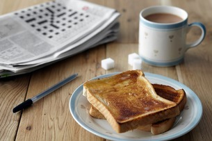 Kitchen table still life with crossword, toast and teaの写真素材 [FYI03507514]