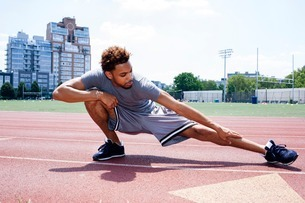 Young man stretching leg on running trackの写真素材 [FYI03507586]