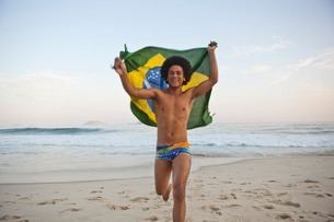 Young man running on beach with Brazilian Flagの写真素材 [FYI03507727]