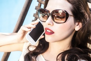 Brunette woman on cell phone wearing sunglassesの写真素材 [FYI03507733]