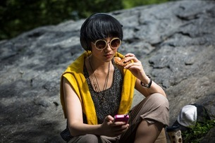 Young woman eating snack with mp3 playerの写真素材 [FYI03507906]