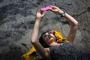 Young woman lying on rocks listening to mp3 playerの写真素材 [FYI03507911]