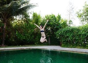 Girl jumping into swimming poolの写真素材 [FYI03507919]