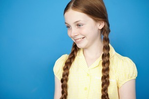 Portrait of girl with plaits wearing yellow school dressの写真素材 [FYI03507974]