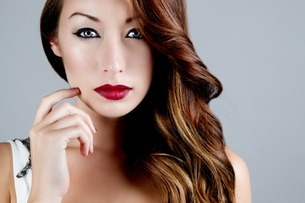 Studio portrait of brunette woman touching cheekの写真素材 [FYI03508056]