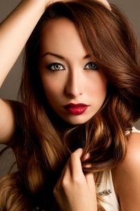 Studio portrait of brunette woman with hands in hairの写真素材 [FYI03508063]