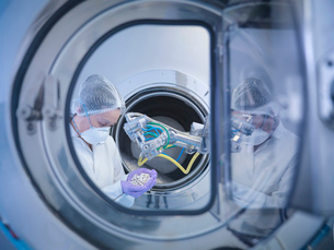 Worker inspects tablets in coating machine in pharmaceutical factoryの写真素材 [FYI03508075]