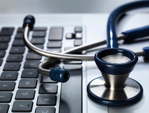 Stethoscope sitting on laptop illustrating online healthcare and doctor's deskの写真素材 [FYI03508105]