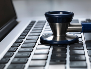 Stethoscope sitting on laptop illustrating online healthcare and doctor's deskの写真素材 [FYI03508106]