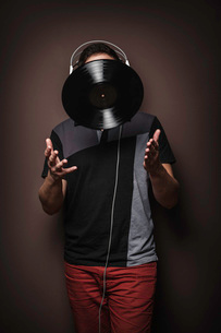 Young man wearing headphones throwing vinyl recordの写真素材 [FYI03508203]