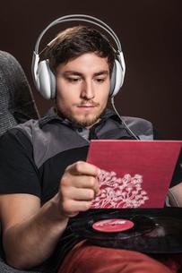 Young man wearing headphones listening to vinyl recordの写真素材 [FYI03508205]