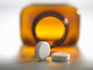 Pain killers pouring from brown medicine bottleの写真素材 [FYI03508296]