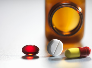Pain killers pouring from brown medicine bottleの写真素材 [FYI03508297]
