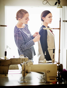 Seamstress adjusting woman's jacketの写真素材 [FYI03508586]