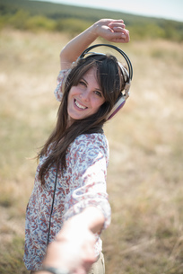 Portrait of mid adult woman dancing in field with arms raised, wearing headphonesの写真素材 [FYI03508675]