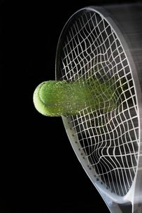 Close up tennis racket hitting ball with blurred motionの写真素材 [FYI03508759]