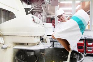 Baker pouring flour into mixerの写真素材 [FYI03508811]