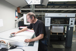 Worker preparing digital printing equipment in print workshopの写真素材 [FYI03508866]