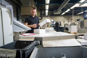 Worker preparing paper for machine in print workshopの写真素材 [FYI03508873]