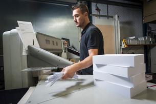Worker disposing of paper trimmings in print workshopの写真素材 [FYI03508874]