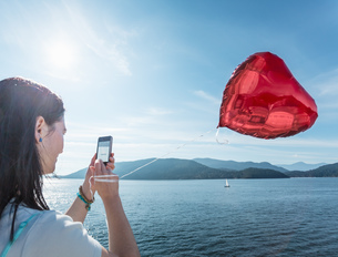 Mature woman photographing heart shaped balloonの写真素材 [FYI03508971]