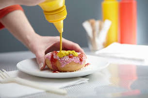 Woman squirting donut with ketchup and mustardの写真素材 [FYI03509019]