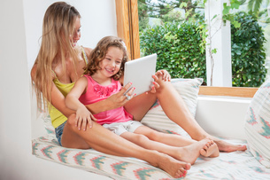 Mother and daughter using digital tabletの写真素材 [FYI03509024]