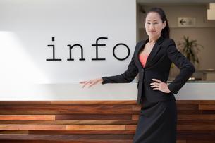 Businesswoman standing at info deskの写真素材 [FYI03509043]