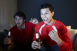 Young men watching sport on tv, holding beer bottleの写真素材 [FYI03509107]