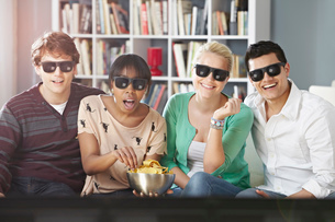 Young people watching 3D television, wearing 3D glassesの写真素材 [FYI03509112]