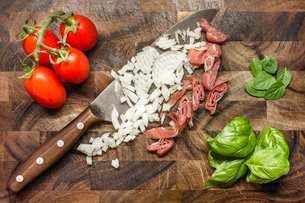 Still life of chopped onion and ham with tomatoes and herbsの写真素材 [FYI03509303]