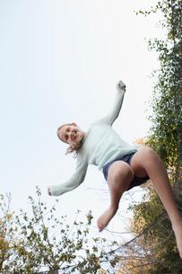 Girl jumping mid air on garden trampolineの写真素材 [FYI03509341]