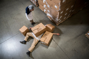 Woman looking at man lying on floor covered by cardboard boxes in warehouseの写真素材 [FYI03509398]