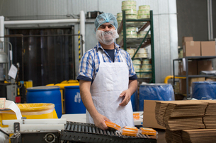 Man packaging vegan cheese in warehouseの写真素材 [FYI03509409]