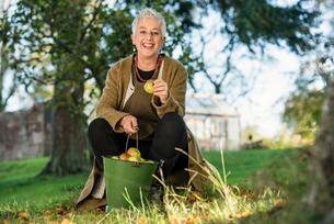Senior woman holding apple from bucketの写真素材 [FYI03509726]