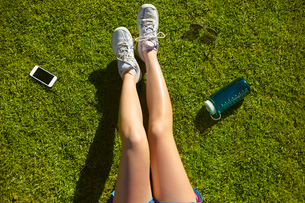 Young woman's legs on sunlit grass in parkの写真素材 [FYI03509795]