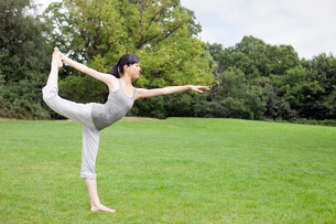 Young woman in park practicing yoga king dancer poseの写真素材 [FYI03509846]