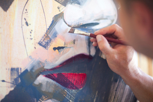 Close up of mature male artist working on canvasの写真素材 [FYI03509868]