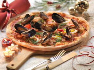 Homemade seafood pizza topped with calamari, prawns and mussels with festive decorationsの写真素材 [FYI03510029]
