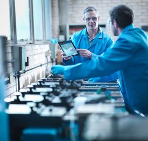Workers using digital tablet for testing springs in laboratoryの写真素材 [FYI03510056]