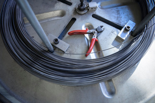 Coil of wire and wire cutters in factoryの写真素材 [FYI03510061]